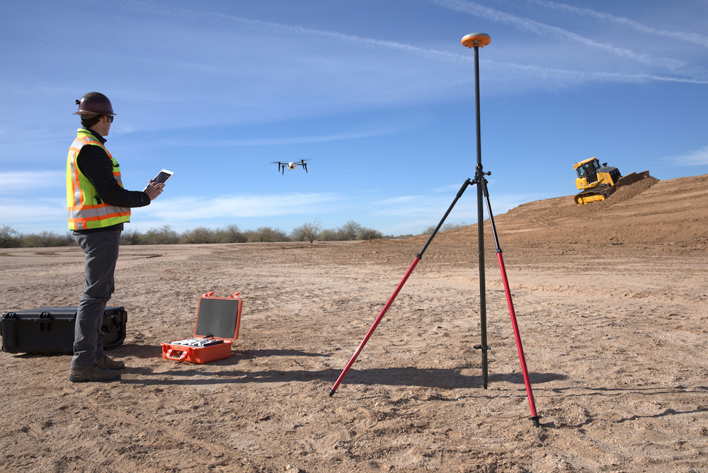 Worker flying Kespry drone on a work site.