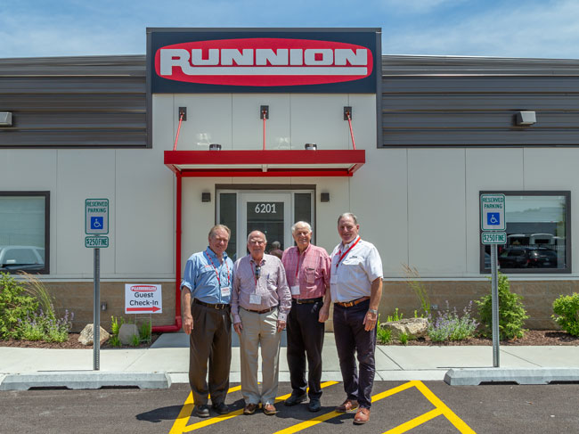 Management standing in front of Runnion Equipment Co.