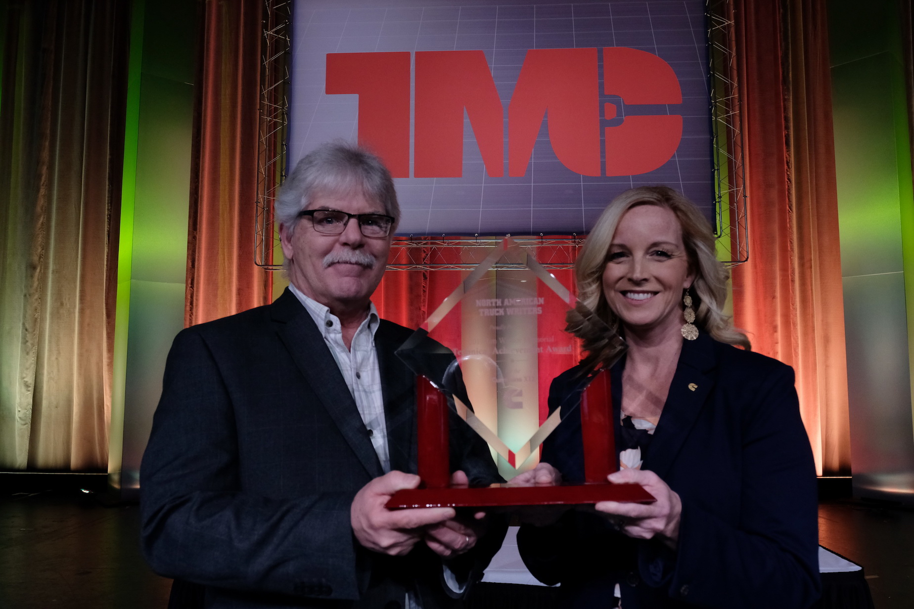 Krista Toenjes, Cummins' North American manager of on-highway sales and marketing, accepts this year's Technical Achievement Award from Jim Park, chairman of the truck writers committee.