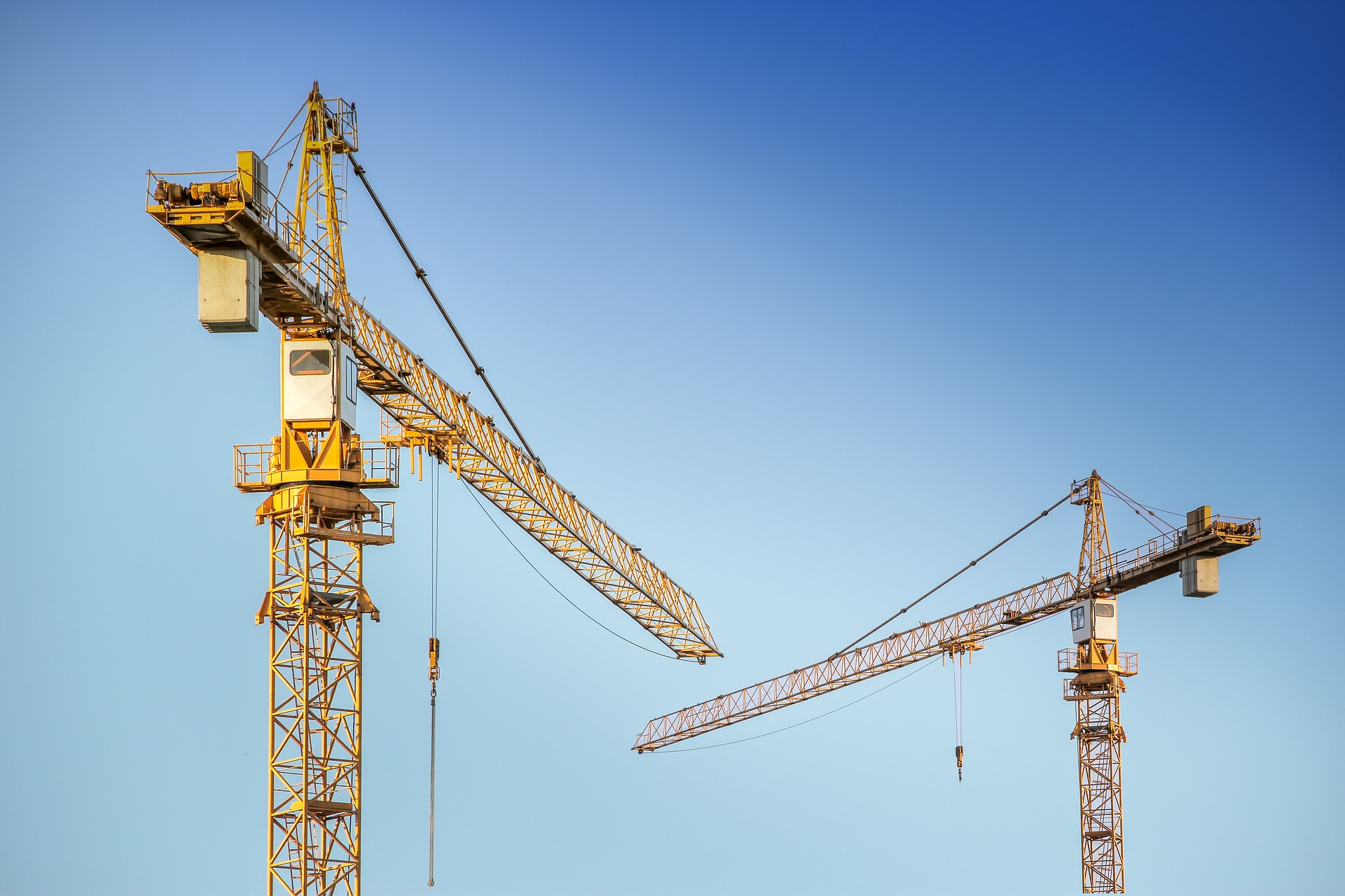 Cranes on site against a blue sky.
