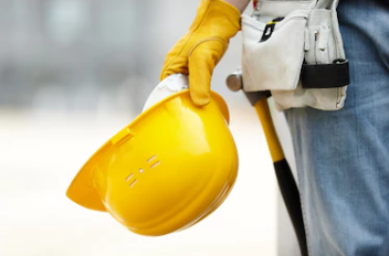 Construction worker holding a hard hat on site.