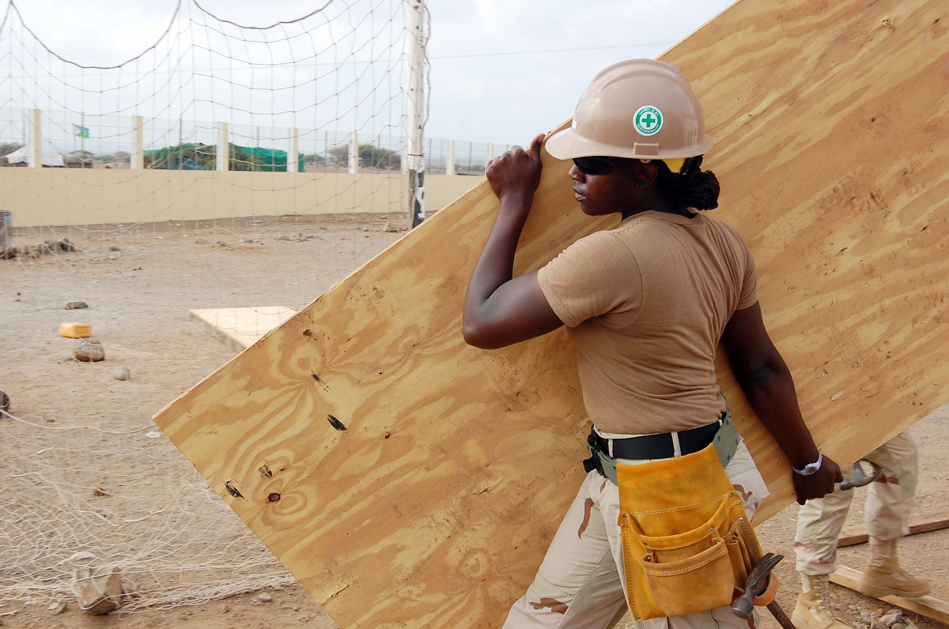 Woman carrying plywood on a construction site.