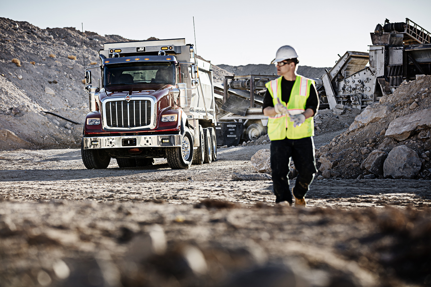 Worker on site, with a Navistar truck in the background.