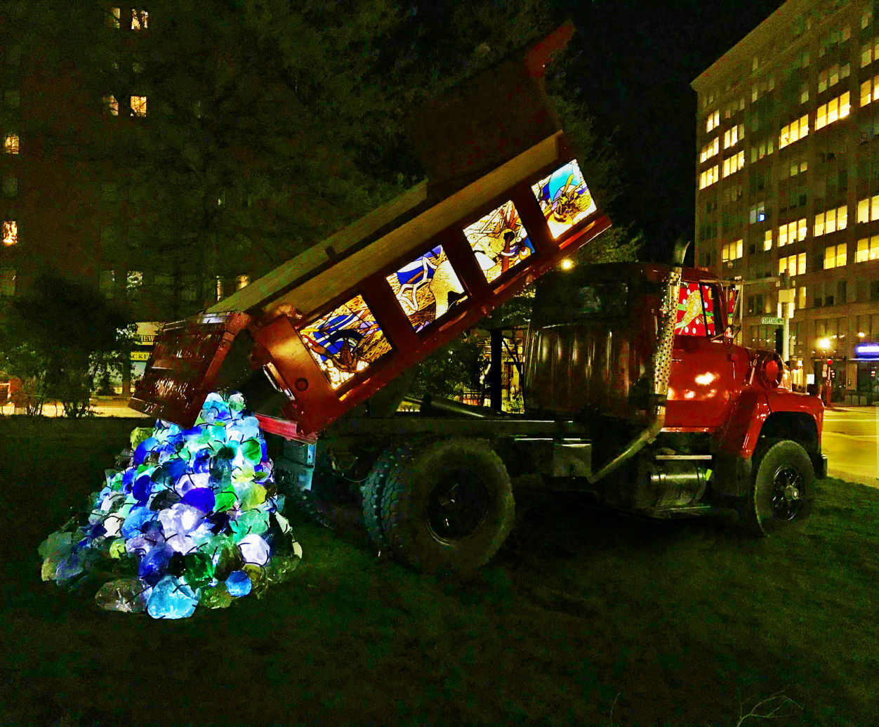 "Artist Karl Unnasch has created a stained glass dump truck to be placed in Boston's ""The Auto Show"" art exhibit."
