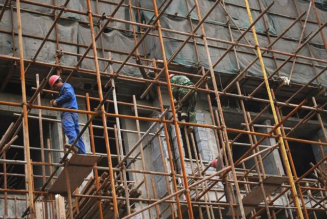 Stock photo shows men on scaffolding.