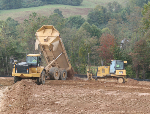 A DXI articulated dump truck spreads material for a GPS-equipped dozer to grade.
