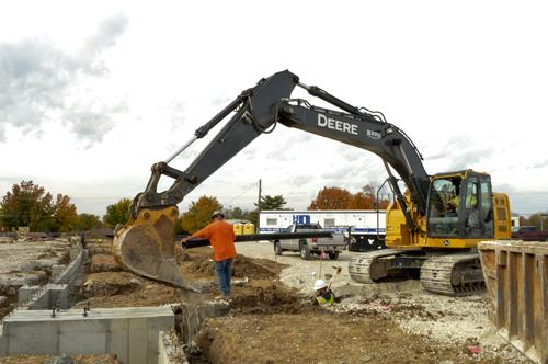 Workers lay pipe on one of Rees Construction's site-prep projects.