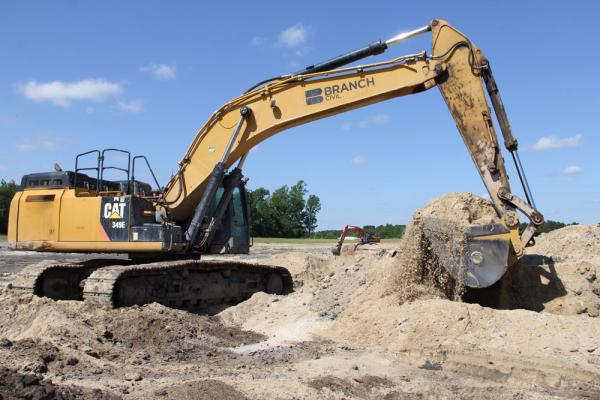 An excavator digs fill material for a highway project.