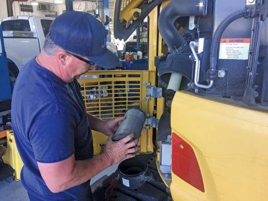 A Sarasota County technician checks the air filter on a compact excavator.