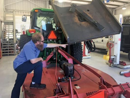 A technician points out a wear area on one of the county's mowers.
