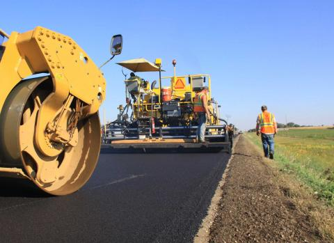 Asphalt mat being laid by compactor and paver