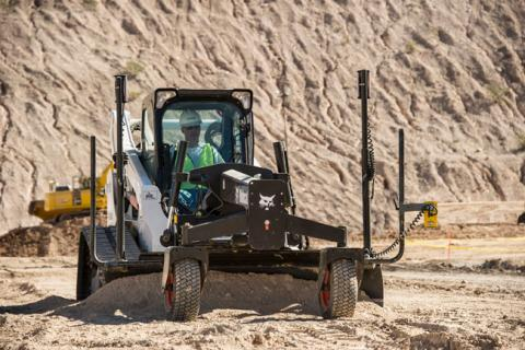 A skid steer loader uses grade control on the job site.