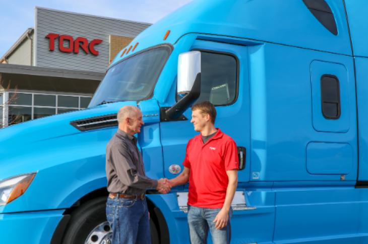 Roger Nielsen, Daimler Trucks, shakes hands with Michael Fleming, Torc.