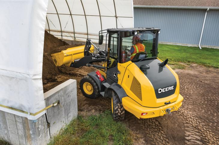 A compact wheel loader moves dirt as it manuevers a tight space.