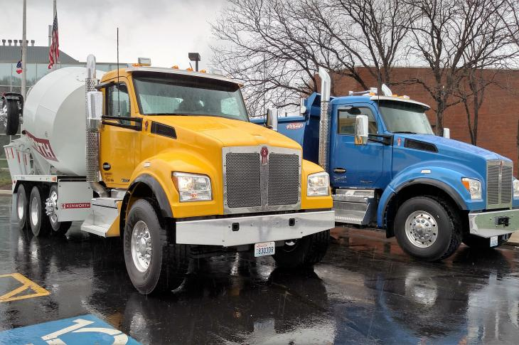 Kenworth T880S mixer and dumper pose in front of Kenworth's plant