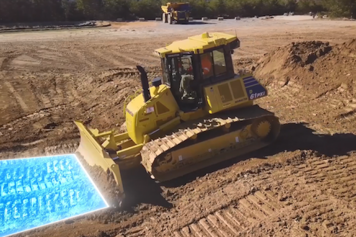 A Komatsu machine uses Dozing Control on a construction site.