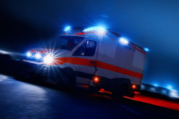 Ambulance illuminated in the dark of night.