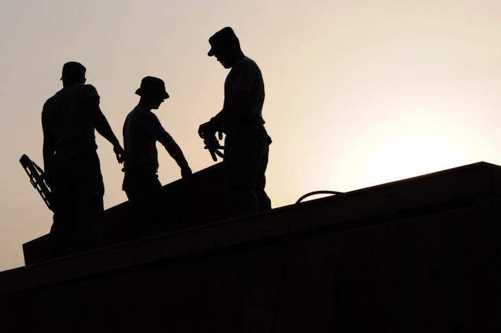 Silhouettes of construction workers on a roof.