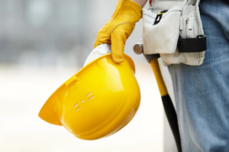 Worker holding a hard hat on site.