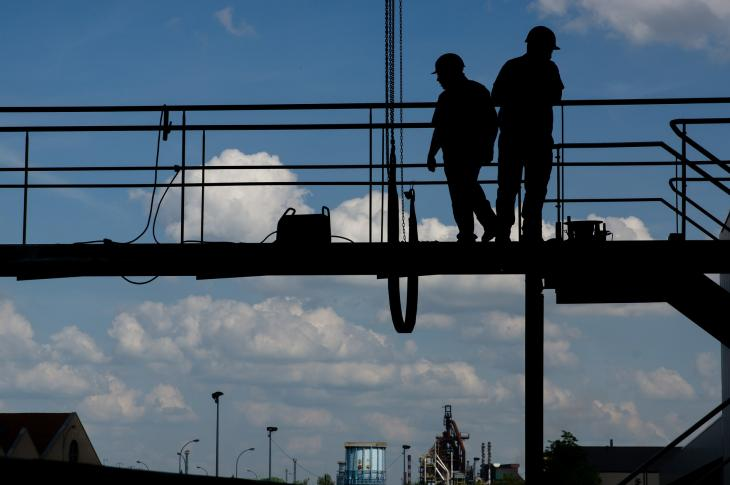 Silhouettes of construction workers on site.