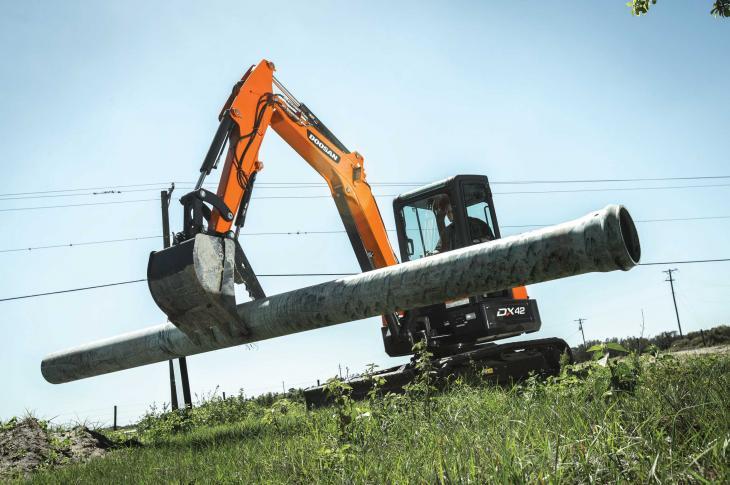 Doosan Infracore excavator lifts a pipe.