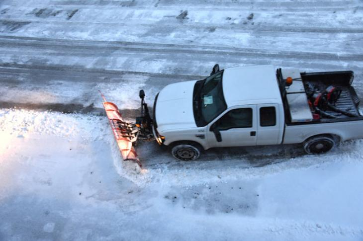 Pickup truck plows snow.