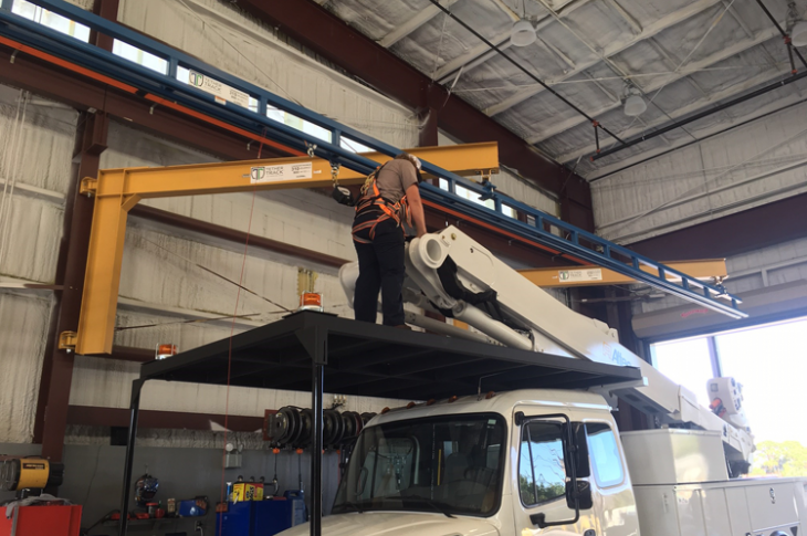 A technician uses fall protection while working above ground level.