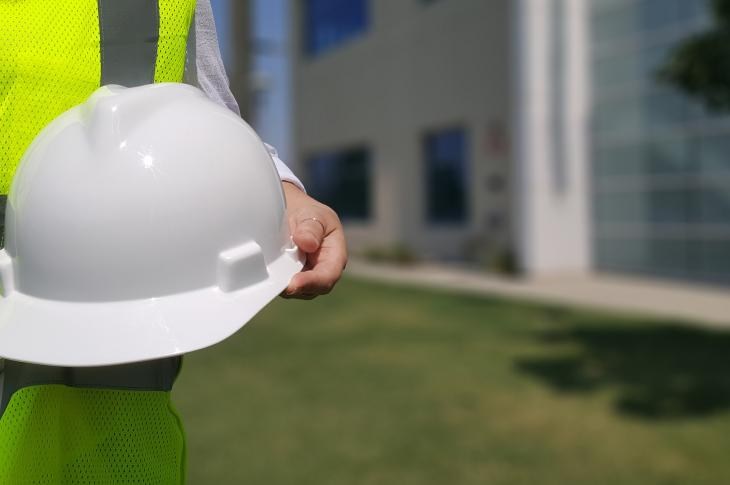 Construction worker holding a white hard hat.