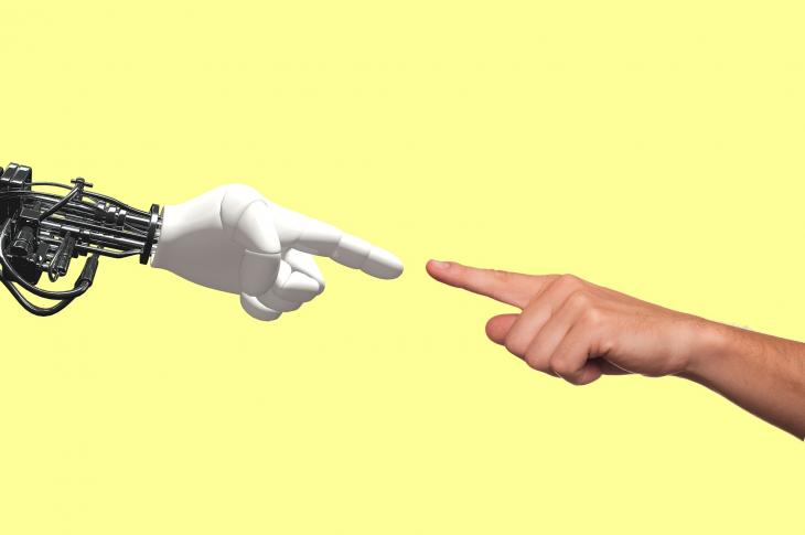 Robot and human hands pointing at each other with an index finger.