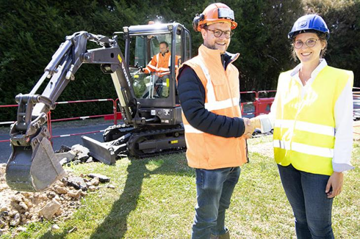 Spac site manager Benjamin Silvent and Volvo CE's electric compact excavator project manager Elodie Guyot in front of the Volvo ECR25 Electric.