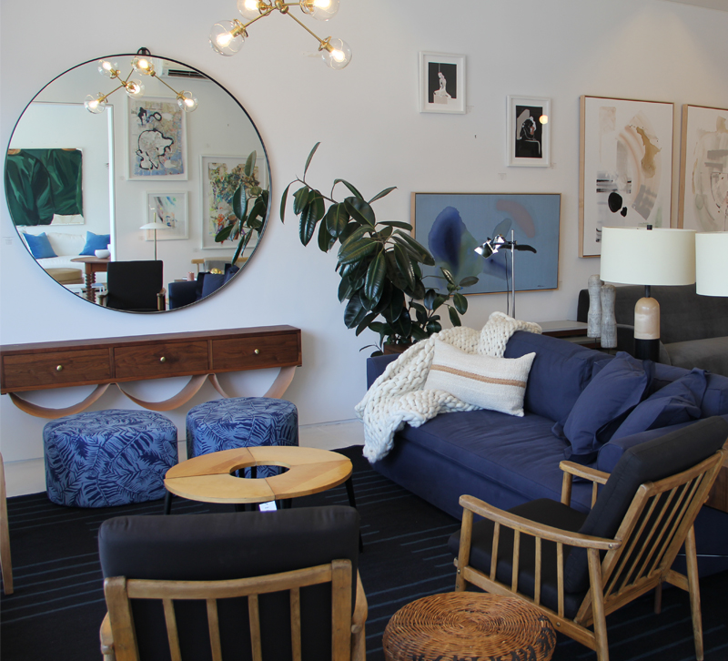 Living room setup in Consort Design showroom with a blue sofa and round wall mirror