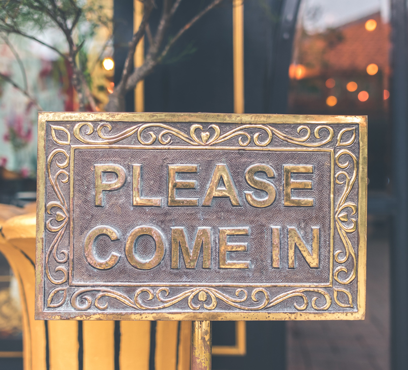 """Store front with a """"Please come in"""" sign on the door"""