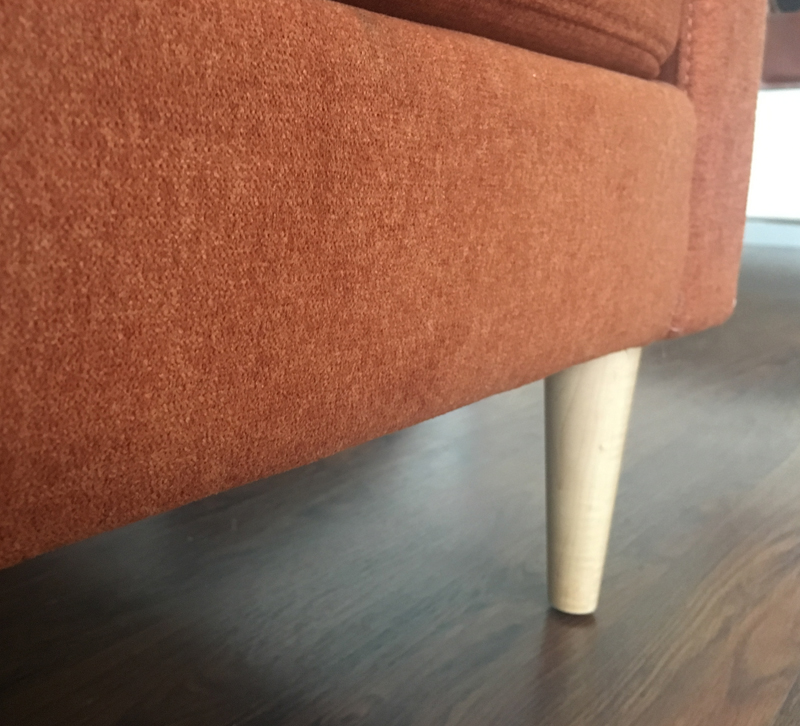 Close up of burnt orange Campaign sofa loveseat bottom and leg