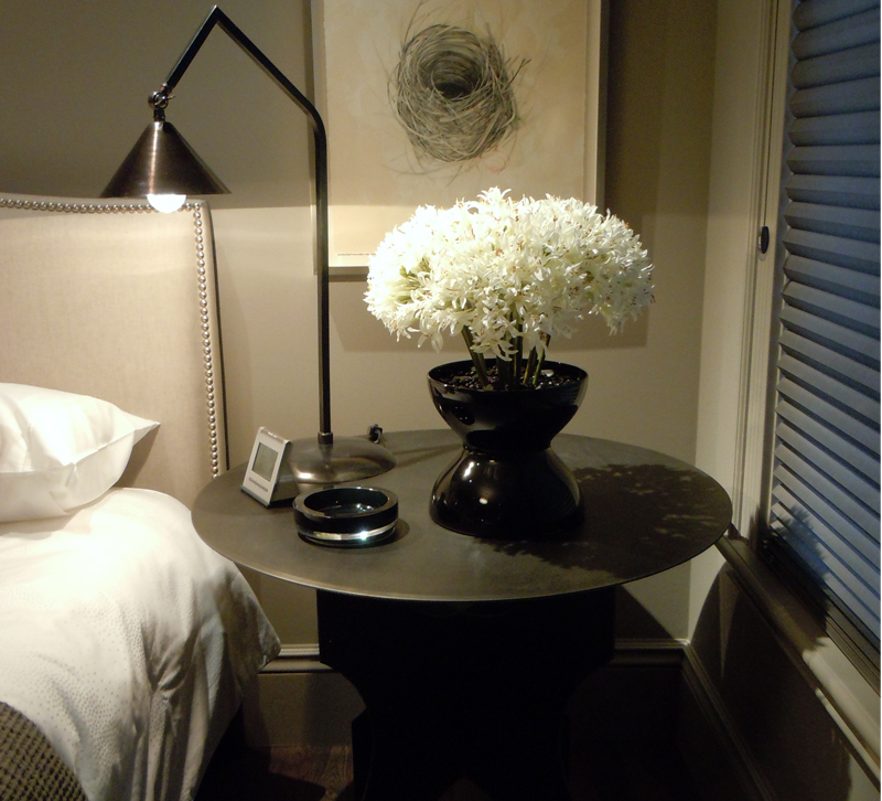 Table with flowers and table lamp next to bed