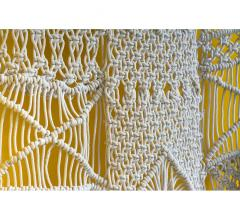 Macrame wall hanging in white on a yellow background from Gold Leaf Design Group