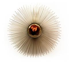 Brilliance Sconce with gold spines that fan out around the light source from Koket
