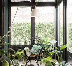 Three-season porch with plants, one chair and a lamp overhead