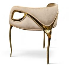 Chandra accent chair with gold arms and a plush seat and back