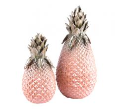 Two metallic pineapple accessories, one large and one small, with green tops and pink bases from Zuo Modern