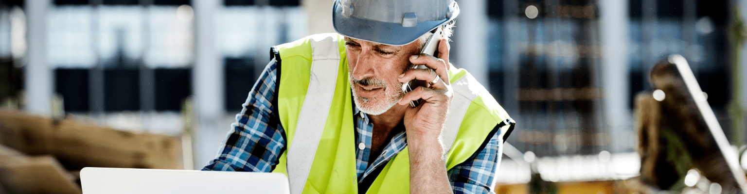 American Express image of construction worker on mobile device