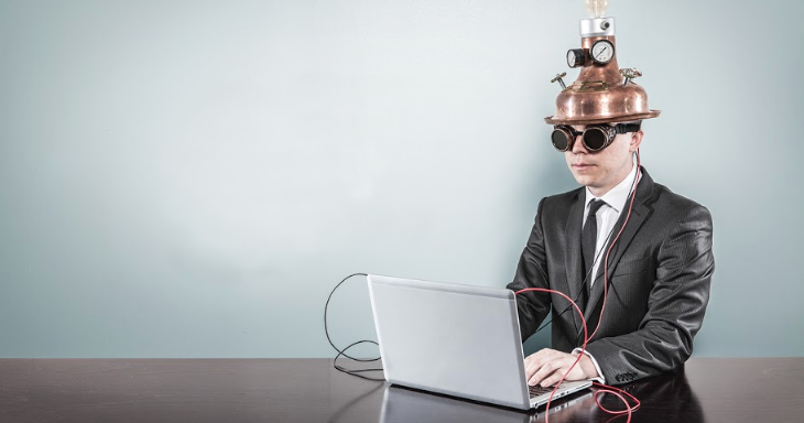 Man sitting with laptop and wearing a time machine helmet