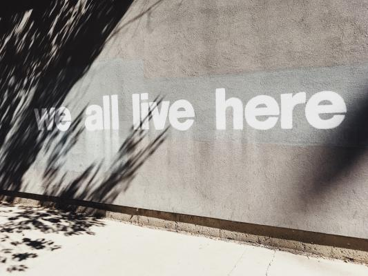 Wall that says 'we all live here'