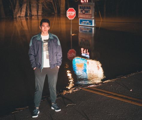 Man standing on flood street in the dark