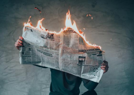 newspaper on fire while a man reads it