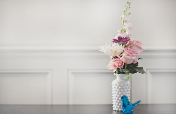 Bouquet of flowers in vase on table with blue bird