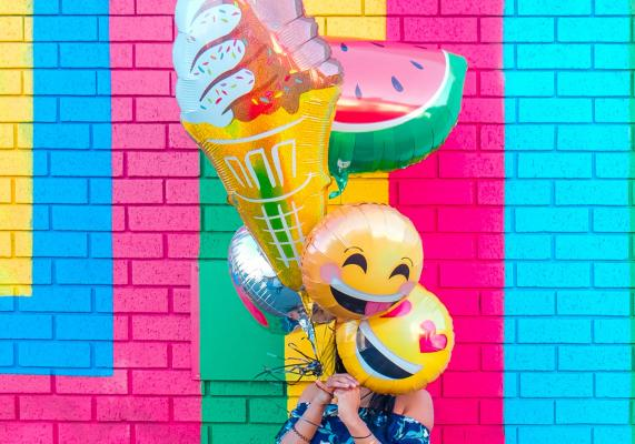 Person holding helium balloons in front of colorful brick wall