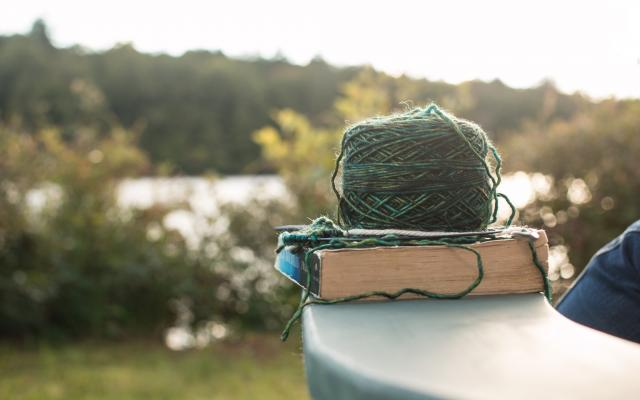 Ball of yarn and book on deck chair in forest