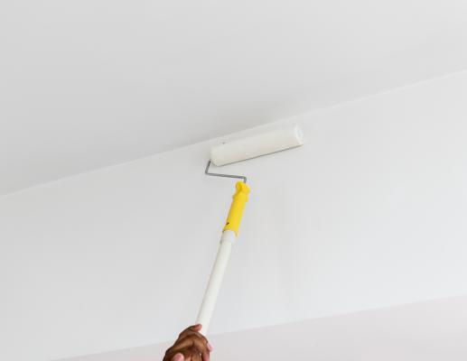 Person with ceiling paint roller