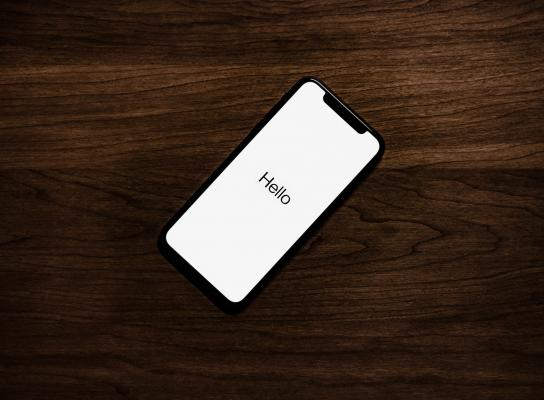 iPhone on table screen reads 'Hello'
