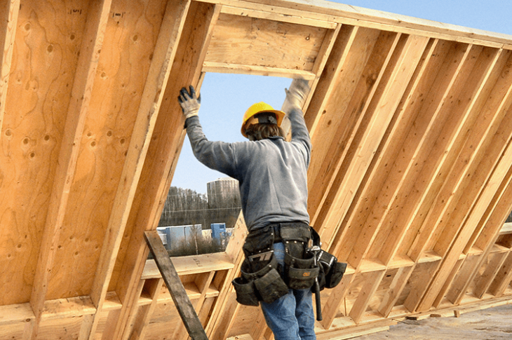 Builders putting up house frame, Photo: AMEX
